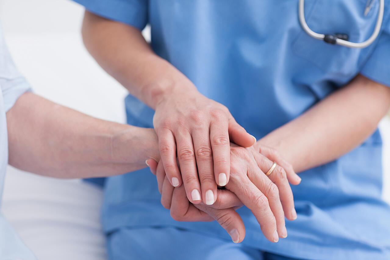 Close up of a nurse touching hand of a patient in hospital ward-1